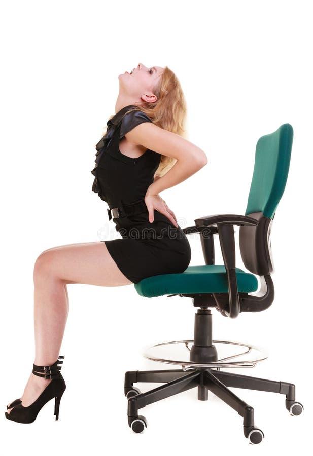 Biznesowej kobiety backache bólu pleców obsiadanie na krześle. Długie godziny pracujące. obrazy royalty free