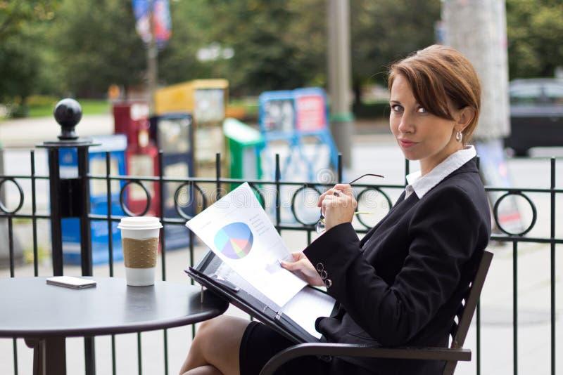 Biznesowej kobiety czytania raportu dokument przy kawiarnią zdjęcia stock