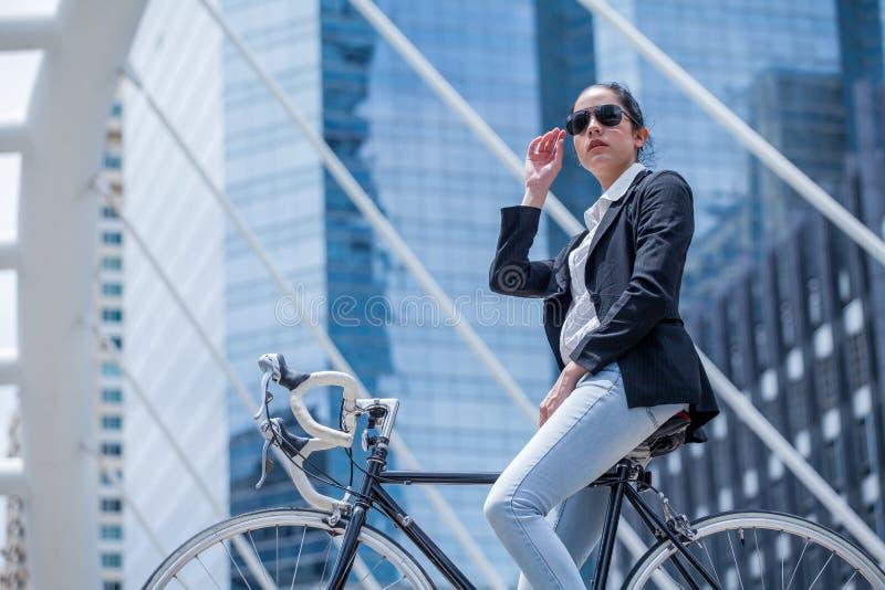 Biznesowej kobiety jeździecki bicykl pracować na miastowej ulicie w mieście transport i zdrowy mody styl życia chłodno mądrze zdjęcia royalty free