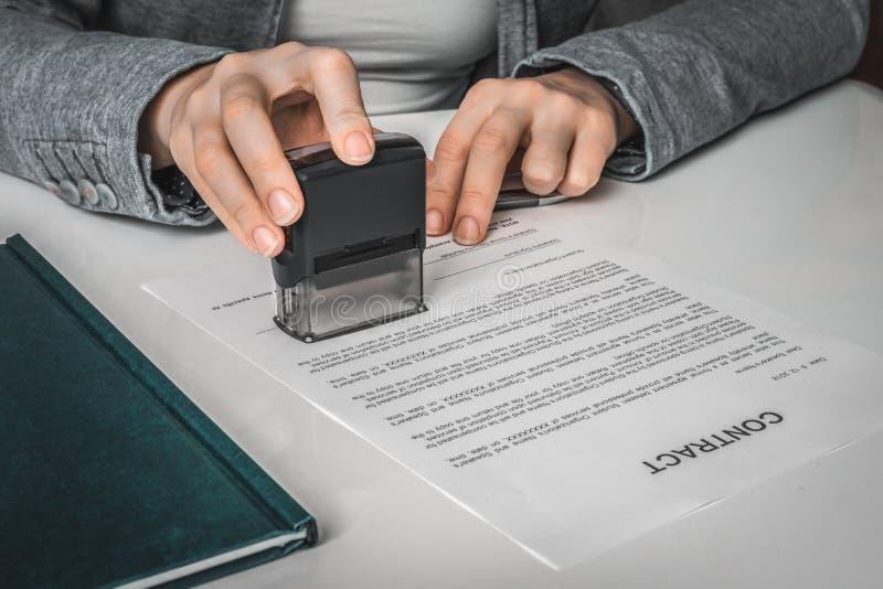Biznesowej kobiety k?adzenia znaczek na dokumentach w biurze fotografia stock