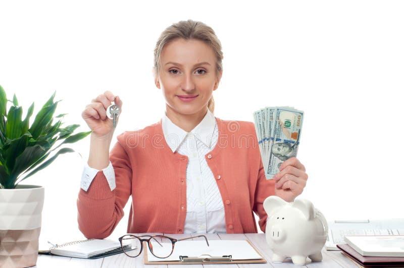 Biznesowej kobiety lub agenta nieruchomości mienia klucze i wiązka pieniędzy banknoty fotografia royalty free