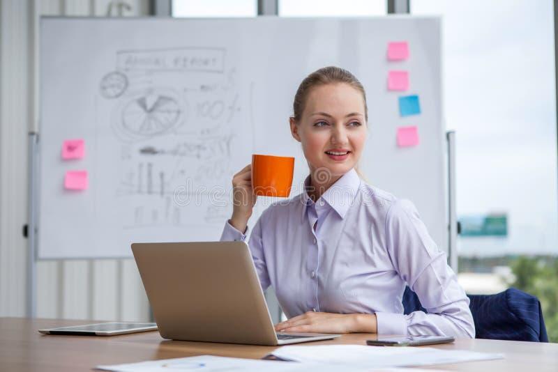 biznesowej kobiety mienie i cieszy się filiżanki obsiadanie przy pracującym miejscem na Białej deski tle obrazy stock