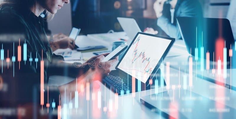 Biznesowej kobiety obsiadania przodu laptop z pieniężnymi wykresami i statystykami na monitorze podw?jny nara?enia szeroki fotografia stock