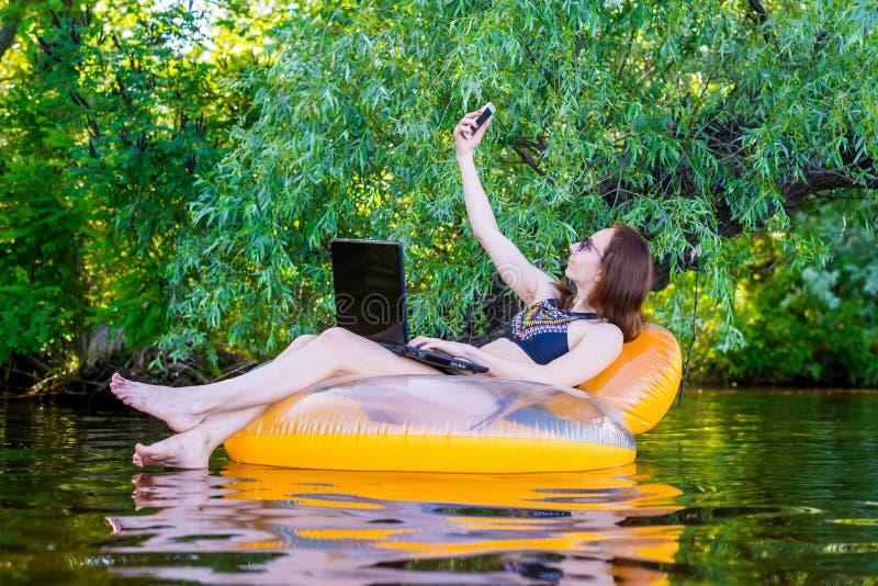Biznesowej kobiety obsiadanie w nadmuchiwanym pierścionku w rzecznej przestrzeni zdjęcia stock
