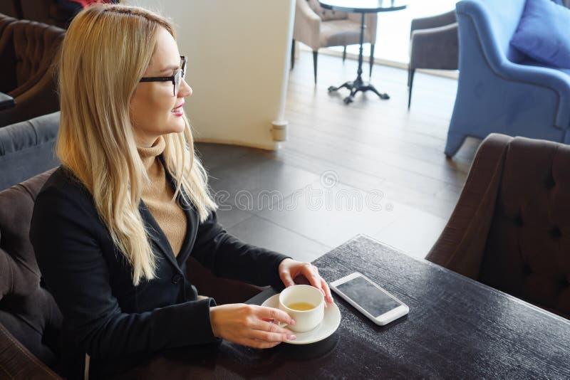 Biznesowej kobiety pi? kawowy i relaksowa? w kawiarni obrazy royalty free