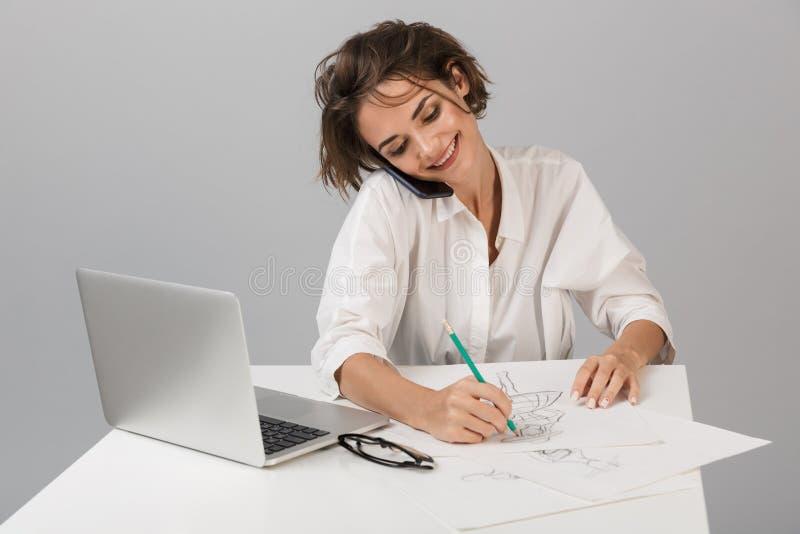 Biznesowej kobiety pozować odizolowywam nad popielatym ściennym tła obsiadaniem przy stołowym używa laptopu rysunkiem opowiada te zdjęcia stock