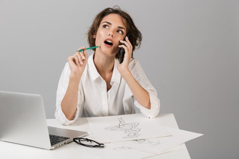 Biznesowej kobiety pozować odizolowywam nad popielatym ściennym tła obsiadaniem przy stołowym używa laptopu rysunkiem opowiada te zdjęcie stock