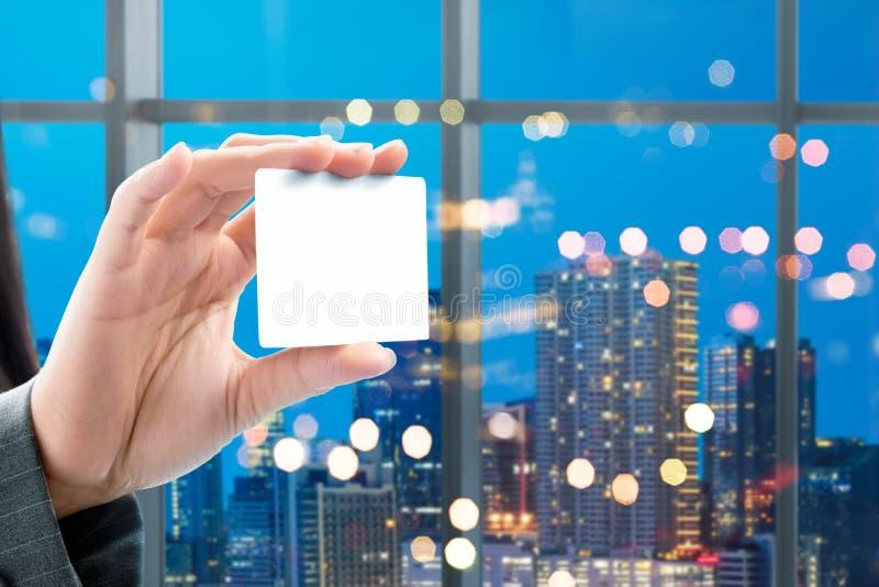 Biznesowej kobiety ręka pokazuje białą pustą kartę na biurze zdjęcia royalty free