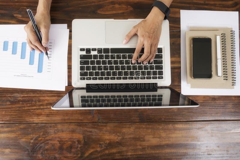 Biznesowej kobiety ręka pracuje z nowym nowożytnym komputerem i biznesowymi mapami fotografia stock
