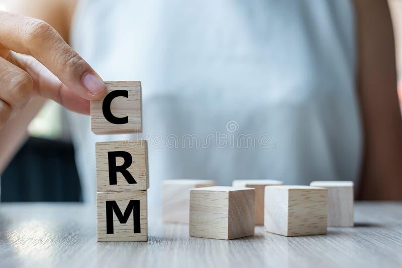 Biznesowej kobiety ręka trzyma drewnianego sześcian z CRM teksta klienta związku zarządzaniem na stołowym tle Pieniężny, marketin zdjęcia royalty free