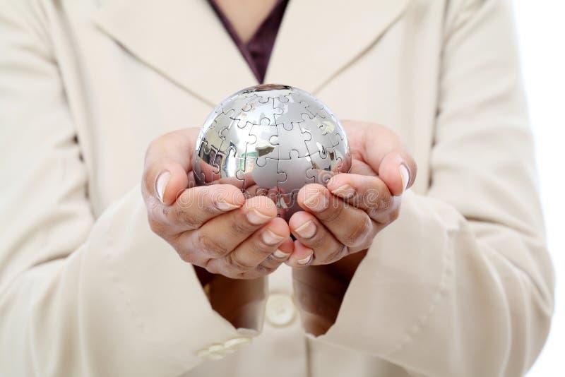 Biznesowej kobiety ręki mienia wyrzynarki łamigłówki kula ziemska zdjęcia royalty free