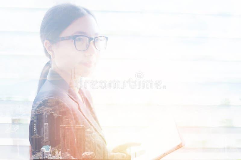 Biznesowej kobiety sukces w kostiumu i eyeglasses - dwoistego ujawnienia kobiet azjatykciej sylwetki oświetleniowi skutki z miast zdjęcie royalty free