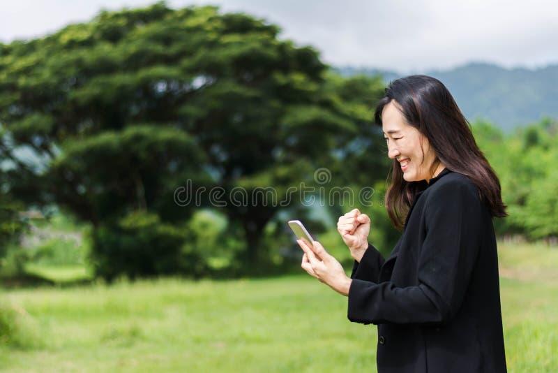 Biznesowej kobiety szczęśliwy patrzeje telefon komórkowy plenerowy z naturą zdjęcia stock