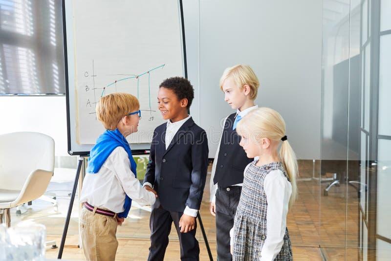 Biznesowi dzieciaki witają each inny z uściskiem dłoni fotografia royalty free
