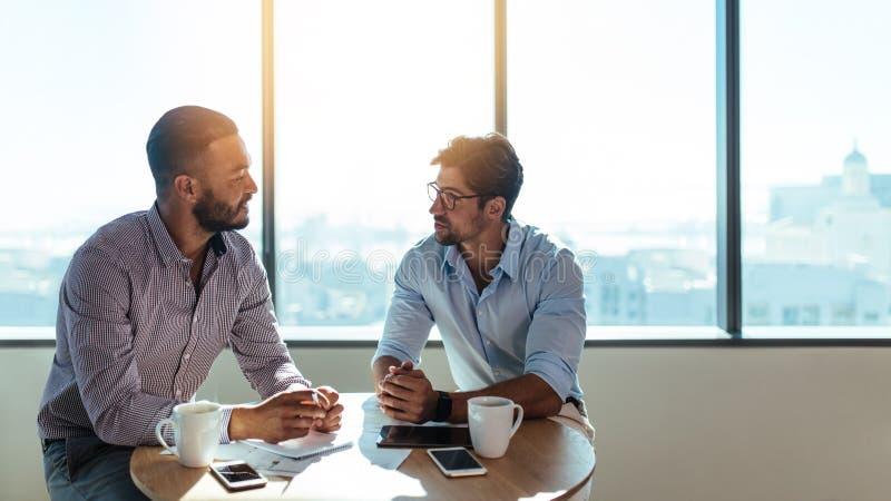 Biznesowi inwestorzy dyskutuje biznes nad filiżanką kawy fotografia stock
