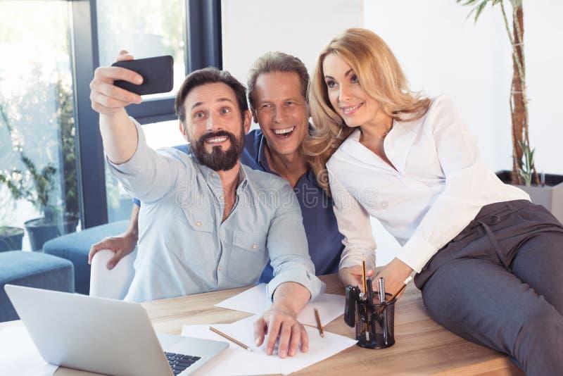 Biznesowi koledzy bierze selfie z smartphone w biurze zdjęcia royalty free