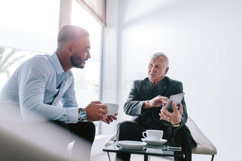 Biznesowi koledzy dyskutuje pracę podczas przerwy obrazy royalty free