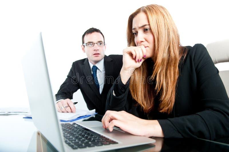 Biznesowi koledzy ono zmaga się z trudną pracą przy biurem zdjęcie royalty free