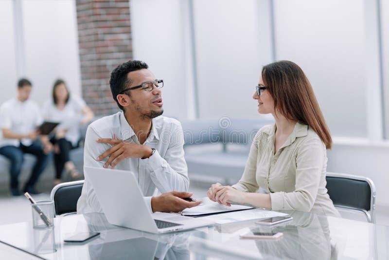 Biznesowi koledzy opowiadaj? obsiadanie przy biurowym biurkiem obraz royalty free