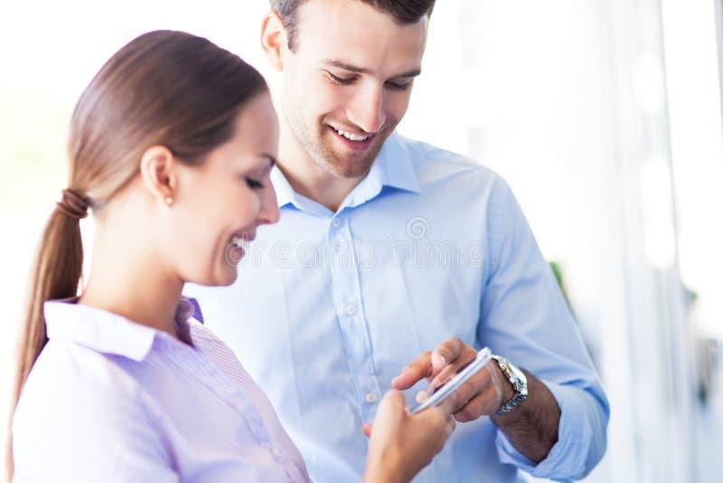 Biznesowi koledzy patrzeje telefon komórkowego obrazy stock
