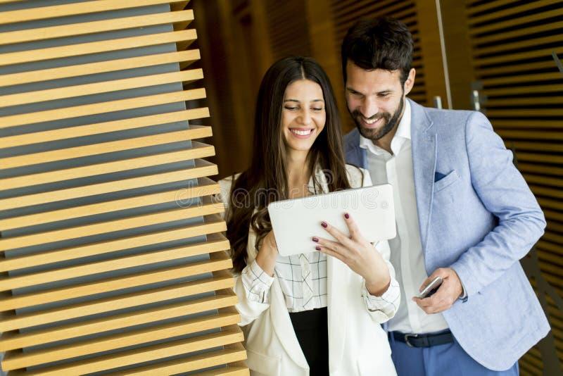 Biznesowi koledzy pracuje cyfrową pastylkę i trzyma zdjęcie stock