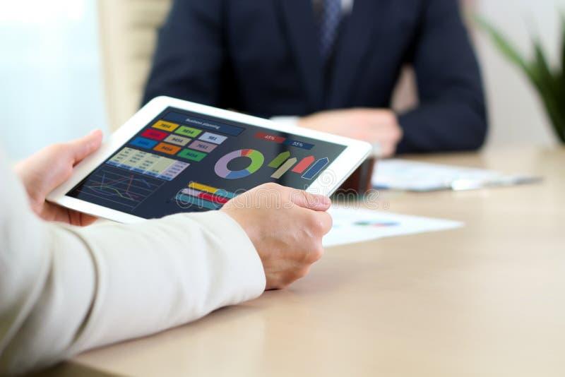 Biznesowi koledzy pracuje i analizuje pieniężne postacie/wykresy na cyfrowej pastylce obrazy stock