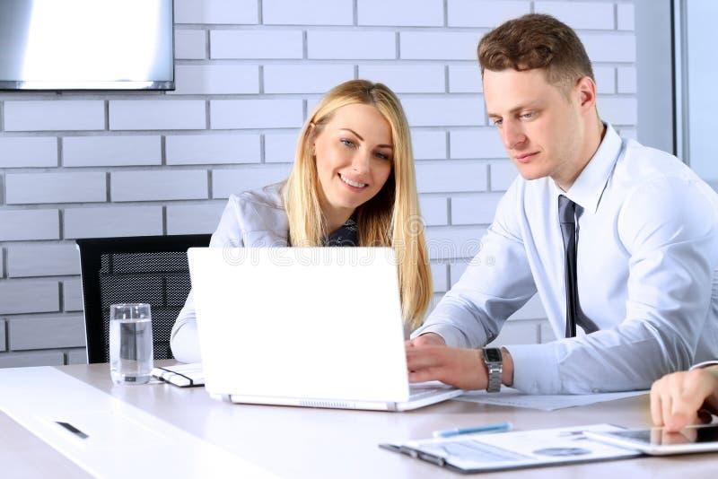 Biznesowi koledzy pracuje i analizuje pieniężne postacie/wykresy na laptopie obraz stock
