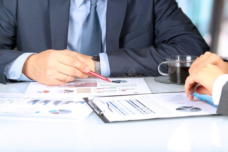 Biznesowi koledzy pracuje wpólnie i analizuje pieniężne postacie na wykresy obraz royalty free