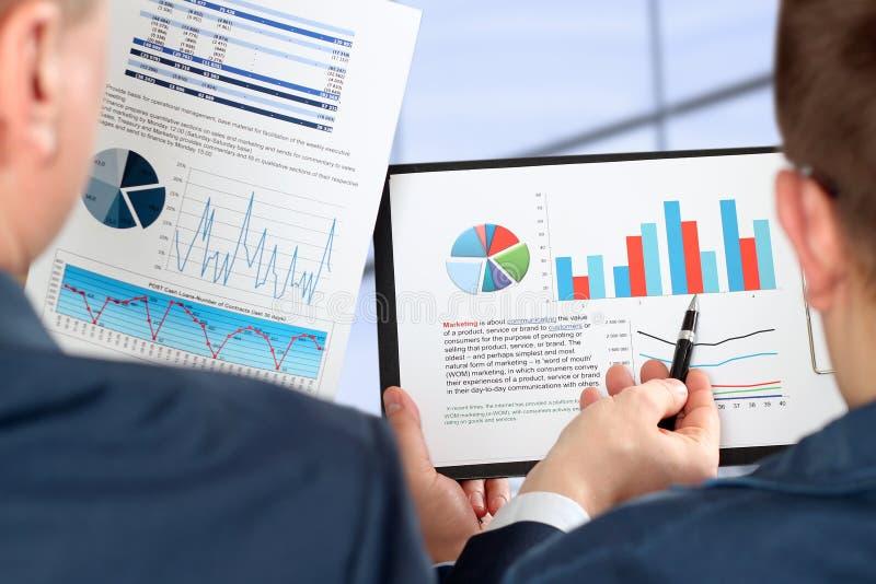 Biznesowi koledzy pracuje wpólnie i analizuje pieniężne postacie na wykresy fotografia royalty free