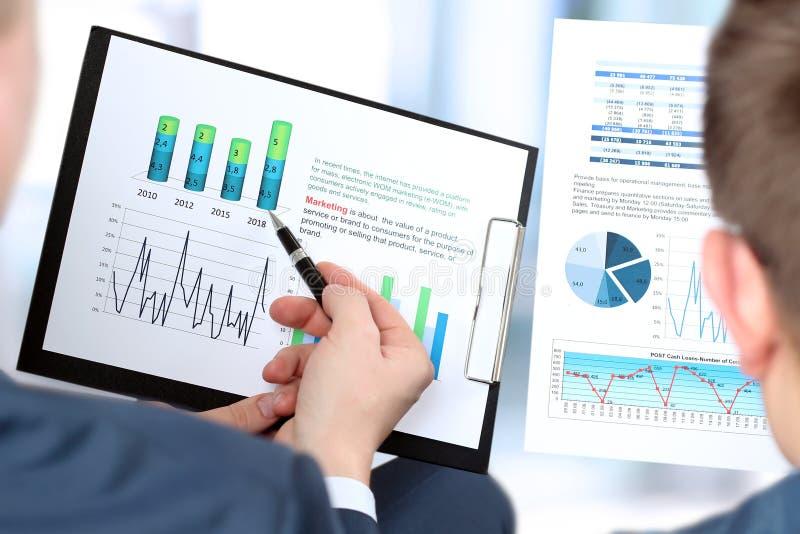Biznesowi koledzy pracuje wpólnie i analizuje pieniężne postacie na wykresy obrazy royalty free