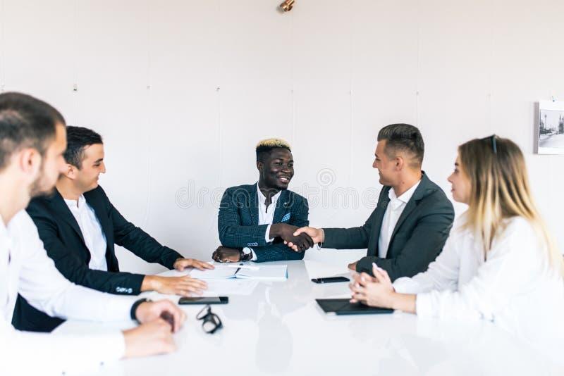 Biznesowi koledzy siedzi przy stołem podczas spotkania z dwa męskimi kierownictwami trząść ręki drużyna pracy zdjęcia royalty free