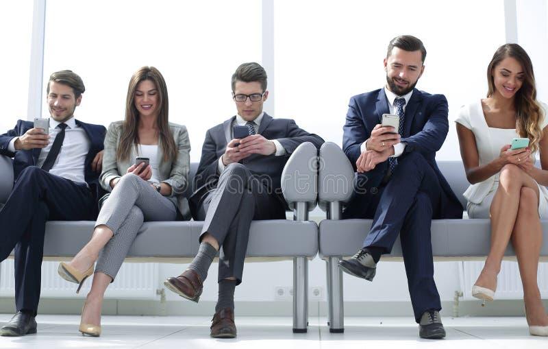 Biznesowi koledzy siedzi w biurowym korytarzu z ich smartphones zdjęcia royalty free
