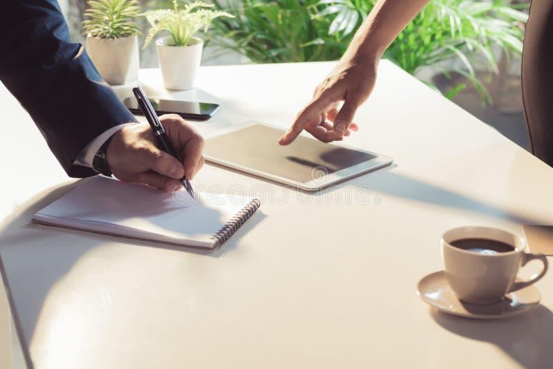 Biznesowi koledzy używa cyfrową pastylkę i brać notatkę przy stołem obrazy stock