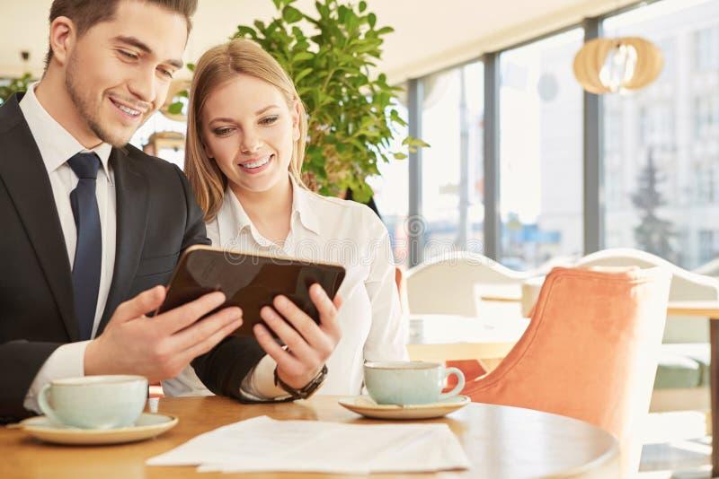 Biznesowi koledzy używa cyfrową pastylkę wpólnie zdjęcie royalty free
