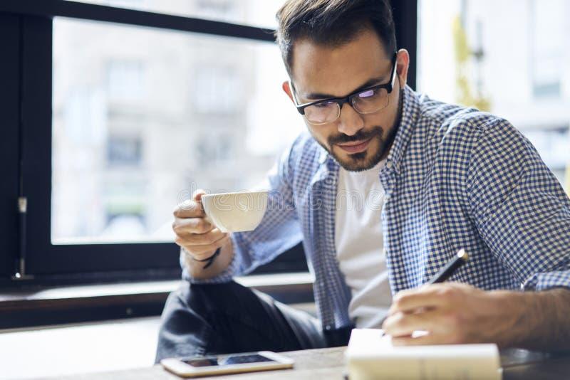 Biznesowi mężczyzna w błękitnym koszulowym obsiadaniu przy stołem w nowożytnej coworking przestrzeni fotografia royalty free