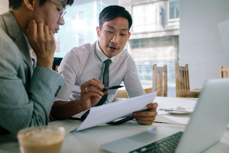 Biznesowi profesjonaliści dyskutuje nad niektóre papierkową robotą zdjęcie royalty free