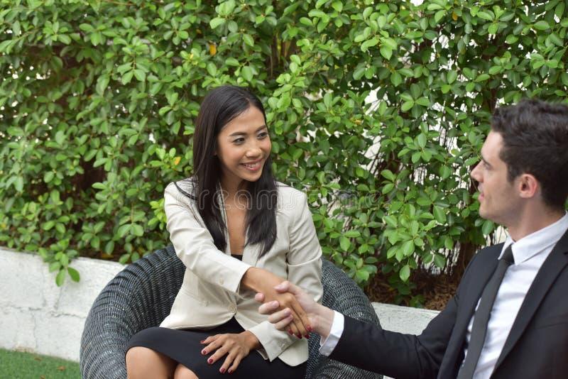 biznesowy ścinku współpraca zawierać ścieżka Młodzi biznesmeni trząść ręki Gdy wiadomość jest dobra zdjęcie royalty free