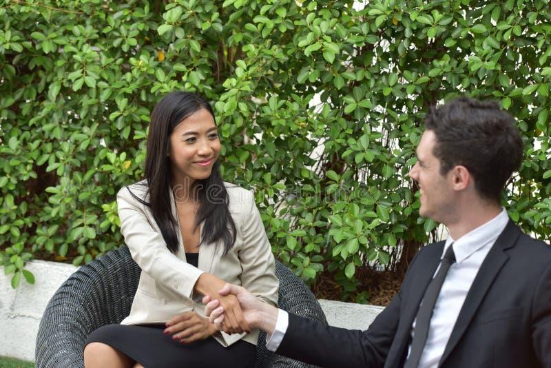 biznesowy ścinku współpraca zawierać ścieżka Młodzi biznesmeni trząść ręki Gdy wiadomość jest dobra zdjęcia stock