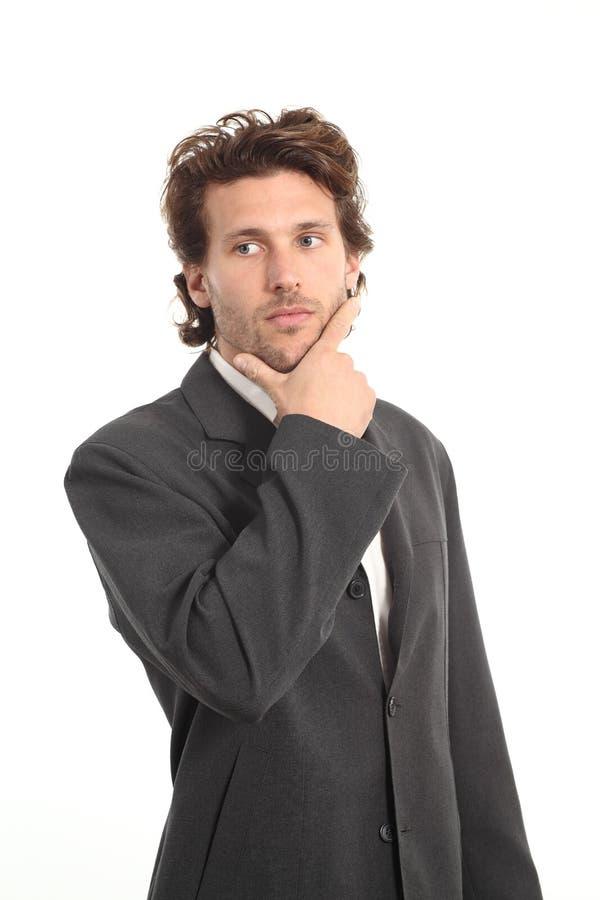 Biznesowy atrakcyjny młodego człowieka główkowanie z ręką na podbródku zdjęcia royalty free