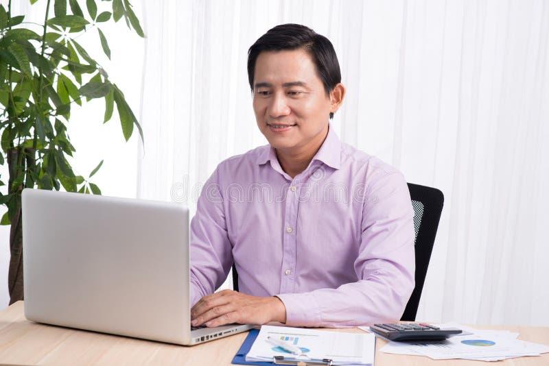 Biznesowy azjatykci mężczyzna obsiadanie przy jego biurkiem pracuje na komputerze i fotografia royalty free