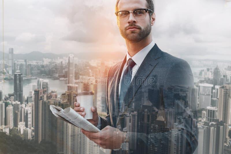 Biznesowy ekspert W górę portreta trzyma popularną gazetę i filiżanka kawy przystojny mężczyzna podczas gdy czekać na obrazy royalty free