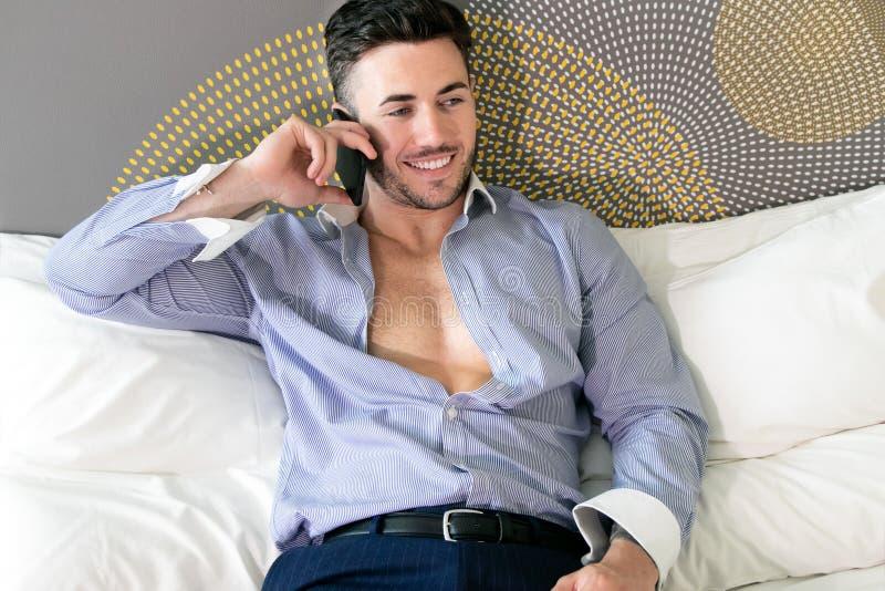 Biznesowy excecutive, fachowy mężczyzna używa telefon komórkowego w pokoju hotelowym, podczas gdy kłamający na łóżku fotografia royalty free