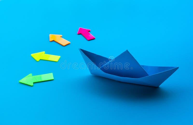 Biznesowy kierunek z łodzi strzałą na błękitnym tle i papierem inwestorscy sukcesów pojęć pomysły zdjęcia royalty free