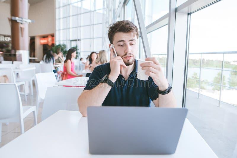 Biznesowy mężczyzna siedzi w kawiarni z laptopem i szkło kawa w jego ręce, mówi telefon komórkowego obraz stock