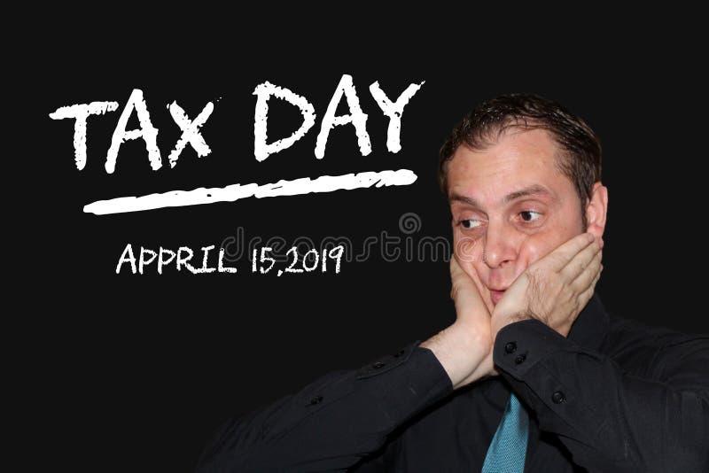 Biznesowy mężczyzna stresujący się przez przybycie podatku dnia - kred słowa na czerni wsiadają zdjęcia stock