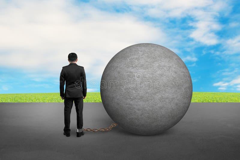 Biznesowy mężczyzna łapać w pułapkę z betonową piłką fotografia stock