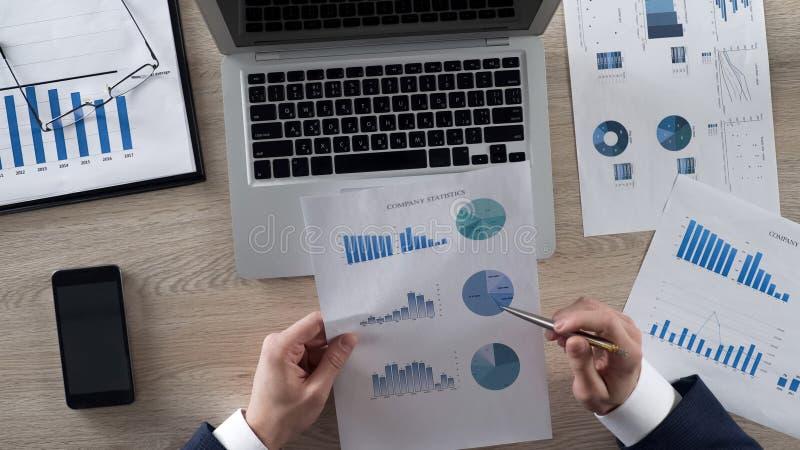 Biznesowy mężczyzna analizuje firm statystyki porównuje mnie z dane na laptopie zdjęcia stock