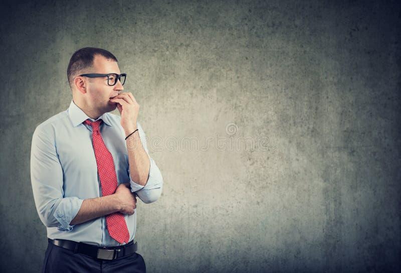 Biznesowy mężczyzna gryźć gwoździe jest w panice i niepokoju patrzeje strona w szkłach zdjęcia royalty free
