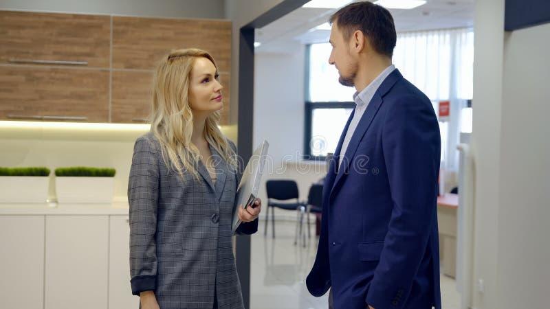 Biznesowy mężczyzna i kobieta dyskutuje nową zgodę w biurze obraz stock