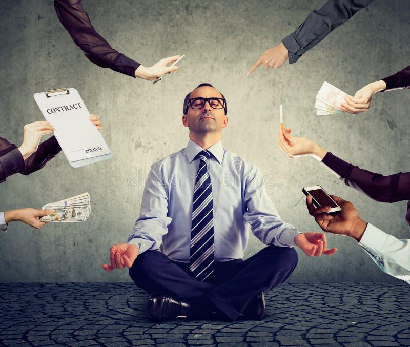 Biznesowy mężczyzna medytuje uśmierzać stres ruchliwie korporacyjny życie obraz royalty free